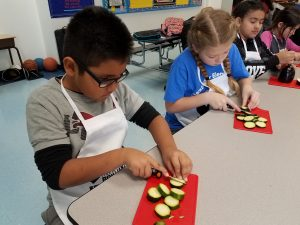A picture of four children cutting up vegetables