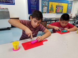 Two boys cutting up pieces of Play-Doh