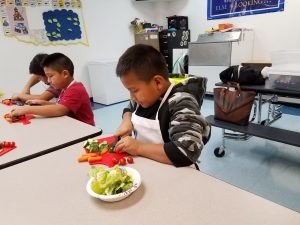 A picture of some boys cutting up vegetables for a salad