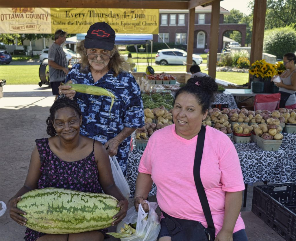 Three people holding corn and watermelon at the Ottawa County Farmer's Market